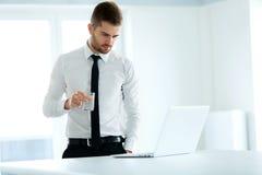 商人研究他的计算机在办公室 图库摄影