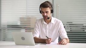 商人穿戴耳机谈话与膝上型计算机的客户写笔记 股票视频