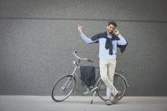 商人站立在自行车旁边和谈话在电话 免版税库存照片