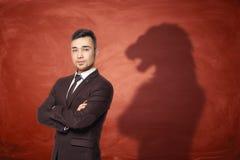 商人站立用手的和他的在红色空的黑板的阴影在看起来狮子后 库存照片