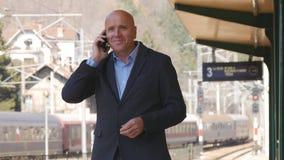 商人等待和谈话与在火车站的手机 免版税库存照片