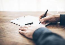 商人签署的合同或文件特写镜头在木书桌上 免版税库存照片