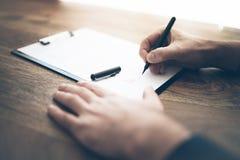 商人签署的合同或文件特写镜头在木书桌上 免版税库存图片
