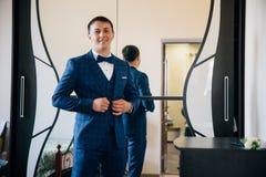 商人紧固他的夹克 在一套美丽的衣服上把放的人,他在他的有一个大镜子的屋子里站立并且微笑 图库摄影