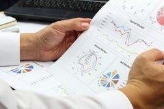 商人综合报告和分析出售的金融市场计划 库存照片