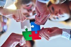 商人编组聚集的七巧板并且代表队支持 免版税库存照片