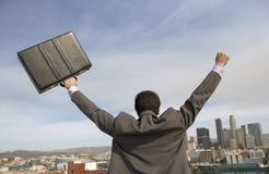 商人背面图与胳膊的在大厦前面 免版税图库摄影