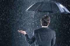 商人背面图在伞下在雨中 免版税库存照片