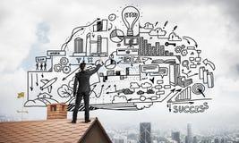 商人背面图在画他新的事务的房子屋顶的 库存照片