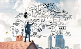 商人背面图在画他新的事务的房子屋顶的 图库摄影