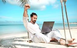 商人自由职业者在与膝上型计算机的海滩 免版税库存照片