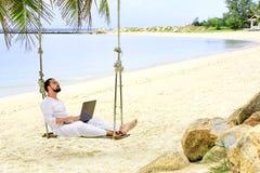 商人自由职业者在与膝上型计算机的海滩 免版税图库摄影