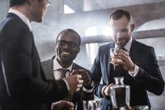 商人花费时间一起喝威士忌酒和抽烟的不同种族的小组 库存照片