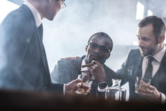 商人花费时间一起喝威士忌酒和抽烟的不同种族的小组 图库摄影