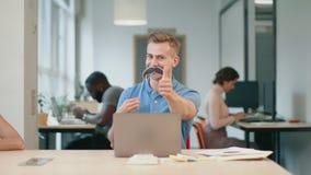 商人获得乐趣在工作场所 闪光眼睛的年轻人看照相机 影视素材