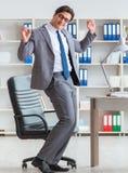 商人获得休假的乐趣在办公室在工作 库存图片