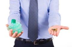 商人藏品被击碎的瓶和硬币。 免版税图库摄影