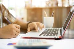 商人行家按在便携式计算机上的和写 免版税库存图片