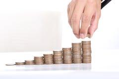 商人被投入的硬币堆金钱 免版税库存照片