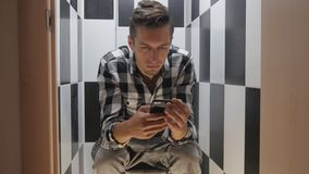 商人观看在电话的新闻坐洗手间 股票视频