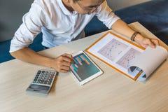商人读的财政数字上面在片剂和文件的 库存照片