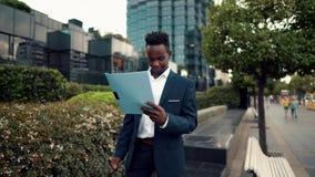 商人读穿着蓝色衣服的文件或笔记本在办公室附近 影视素材
