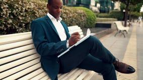 商人读穿着蓝色衣服的文件或笔记本在办公室附近 股票录像