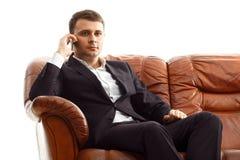 商人谈的电话坐沙发 图库摄影