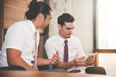 商人谈论与片剂在办公室 免版税库存图片