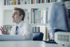 年轻商人谈论在业务会议上与在他后的同事 库存照片