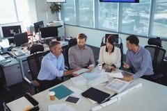 商人谈论在会议在办公桌 库存图片