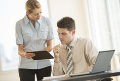商人谈论在数字式片剂在办公室 库存照片