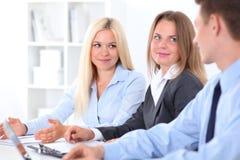 商人谈论想法在会议,在白肤金发的妇女的焦点上 免版税图库摄影