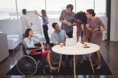 商人谈论战略与残疾同事在创造性的办公室 图库摄影