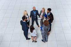 商人谈论的小组会议文件沟通项目的计划,谈的油罐顶部角钢视图 库存照片