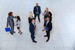 商人谈论的小组会议文件沟通项目的计划,谈的油罐顶部角钢视图 免版税图库摄影