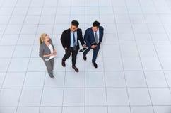 商人谈论的小组会议沟通的步行,谈的油罐顶部角钢视图 免版税图库摄影