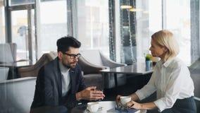 商人谈话与咖啡馆的可爱的成熟妇女工友在桌上 股票录像