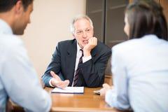 商人谈话与夫妇 免版税库存照片