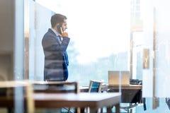 商人谈话在一个手机,当看通过在NY时的窗口 库存图片