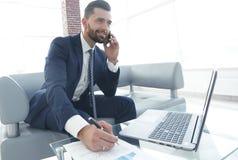 商人谈话在关于财政文件的智能手机 图库摄影