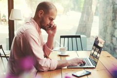 商人谈话在巧妙的电话和神色与膝上型计算机屏幕 库存照片