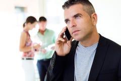 商人谈话在手机在办公室 库存照片