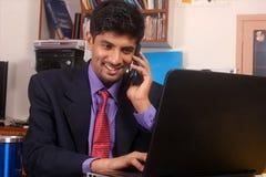 年轻商人谈话在手机在办公室 图库摄影