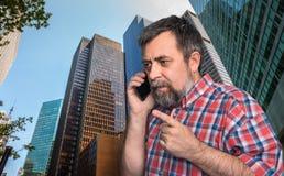 商人谈话在手机在特大的城市 免版税库存图片