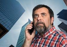 商人谈话在手机在特大的城市 库存图片