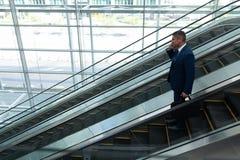 商人谈话在手机,当移动下来在自动扶梯时 免版税库存图片