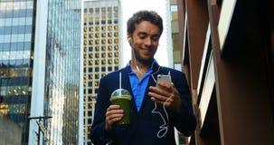 商人谈话在手机,当饮用汁液时