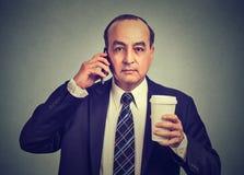 商人谈话在拿着咖啡的手机 免版税图库摄影