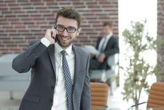 商人谈话在智能手机在他的办公室 库存照片